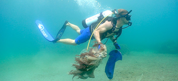 A man scuba diving in blue scuba gear and holding a net filled with trash