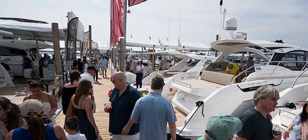 people walking along the dock at an outdoor boat show