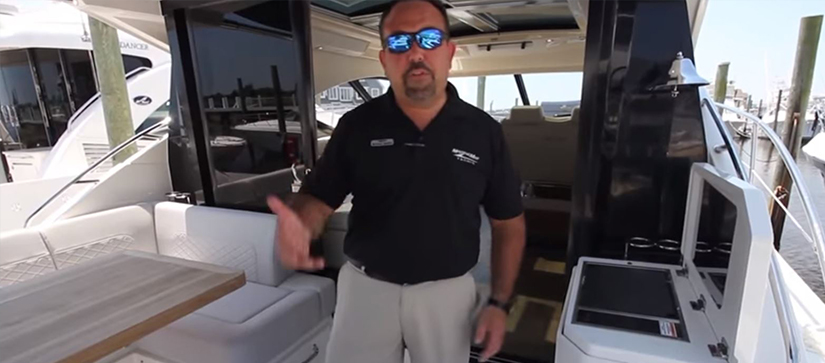 male on aft deck of yacht pointing to features