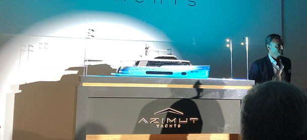 A model of the Azimut S10 in a glass case, being presented at the Cannes Yachting Festival in front of a crowd