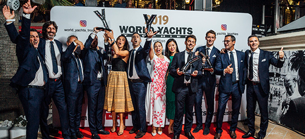 A group of people posing for a photo on a red carpet at the World Yachts Trophies gala, holding up trophies and celebrating