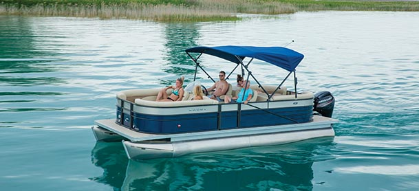 A family on a Crest pontoon as it cruises through clear blue water