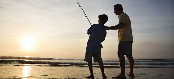 A man and boy fishing in shallow water while standing on sand as the sun sets