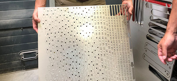 A metal board with small circular holes cut into it, being held up by a man