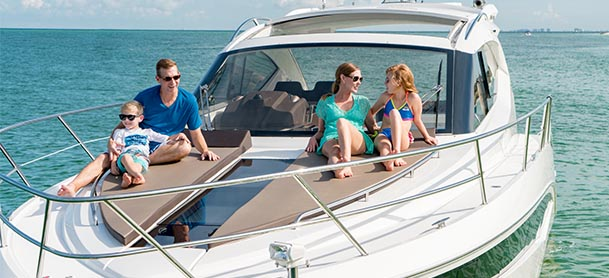 family sitting on the sunpad on the bow of their boat