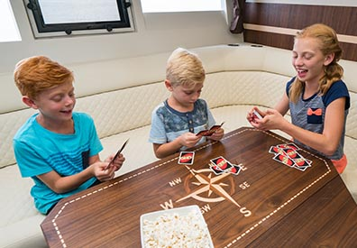 three kids sitting around a table inside a boat playing cards