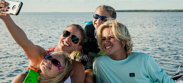 A family smiling for a photo on a boat