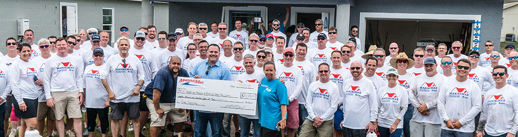 MarineMax team members holding a large check