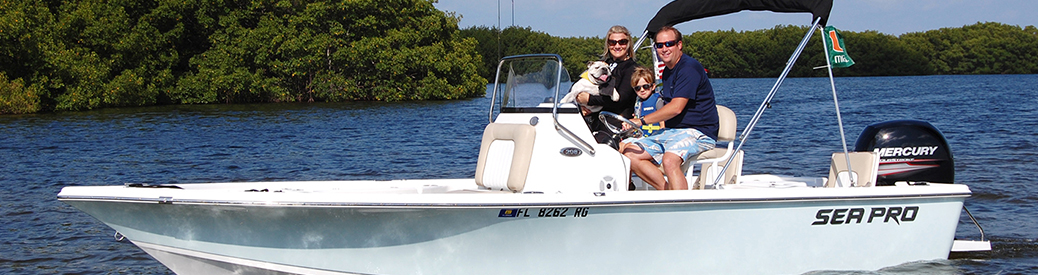male, female, and child with dog riding in a light blue fishing boat