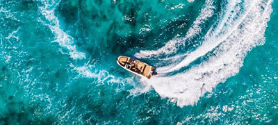 Aerial shot of a boat cruising in a circle, leaving a wake behind it.