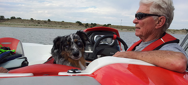 A small dog seated on a boat next to a man in a red life jacket