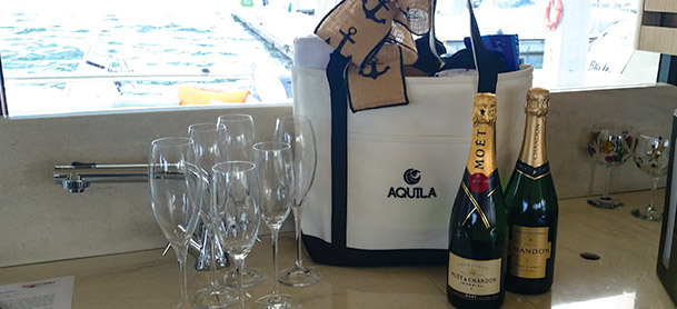 champagne, glassware, and a beach bag sitting on a countertop