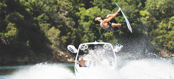 A Tige boat in the water with a wakesurfer