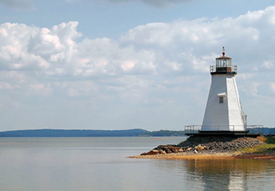 small white lighthouse on the shore