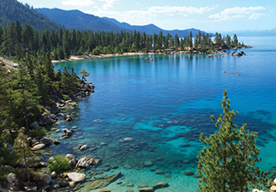 very clear blue turquoise lake with pine trees and mountain in the background