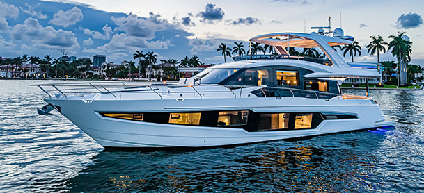 A Galeon 680 Fly resting in open water at sundown with the interior lights on