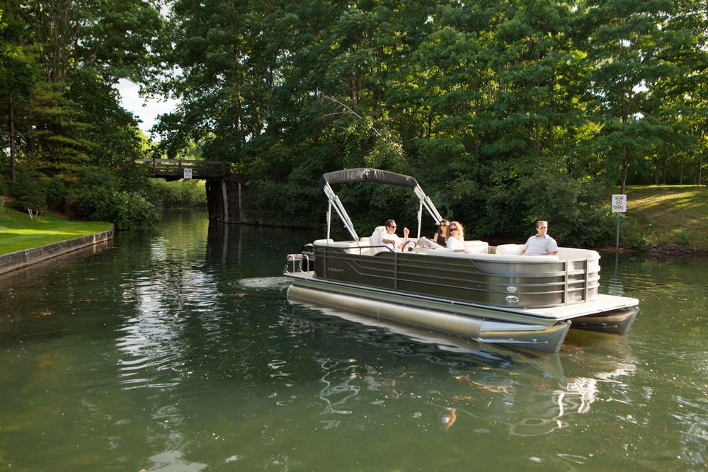 Pontoon boat traveling through waterway with a group onboard