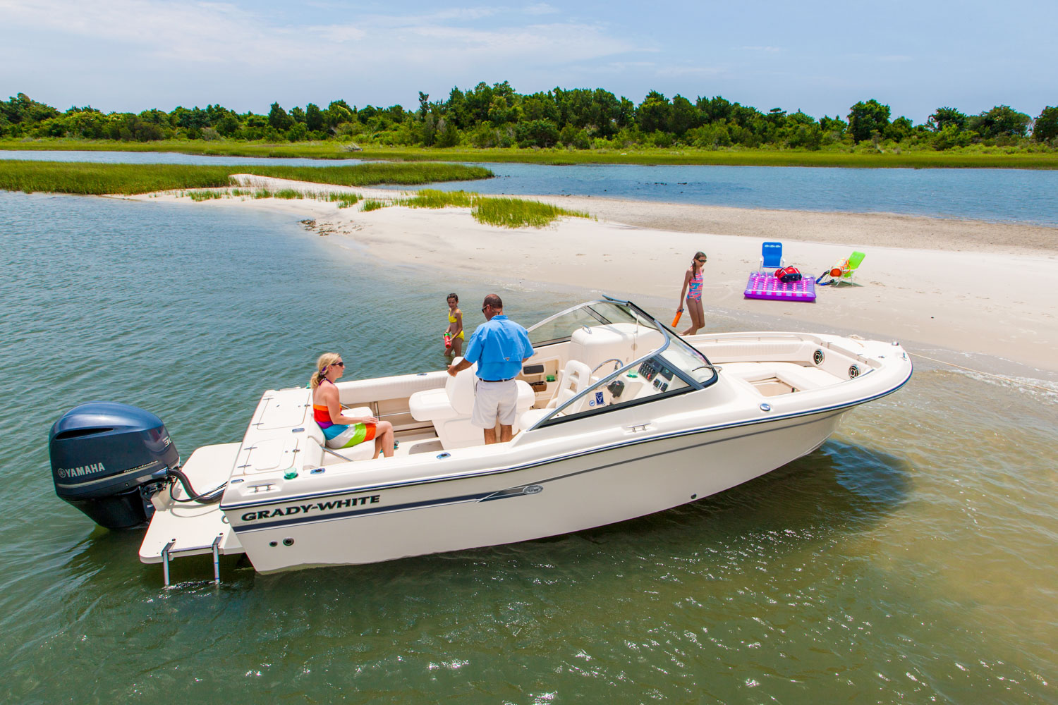 boat docked next to sandbar with family enjoying the water around it