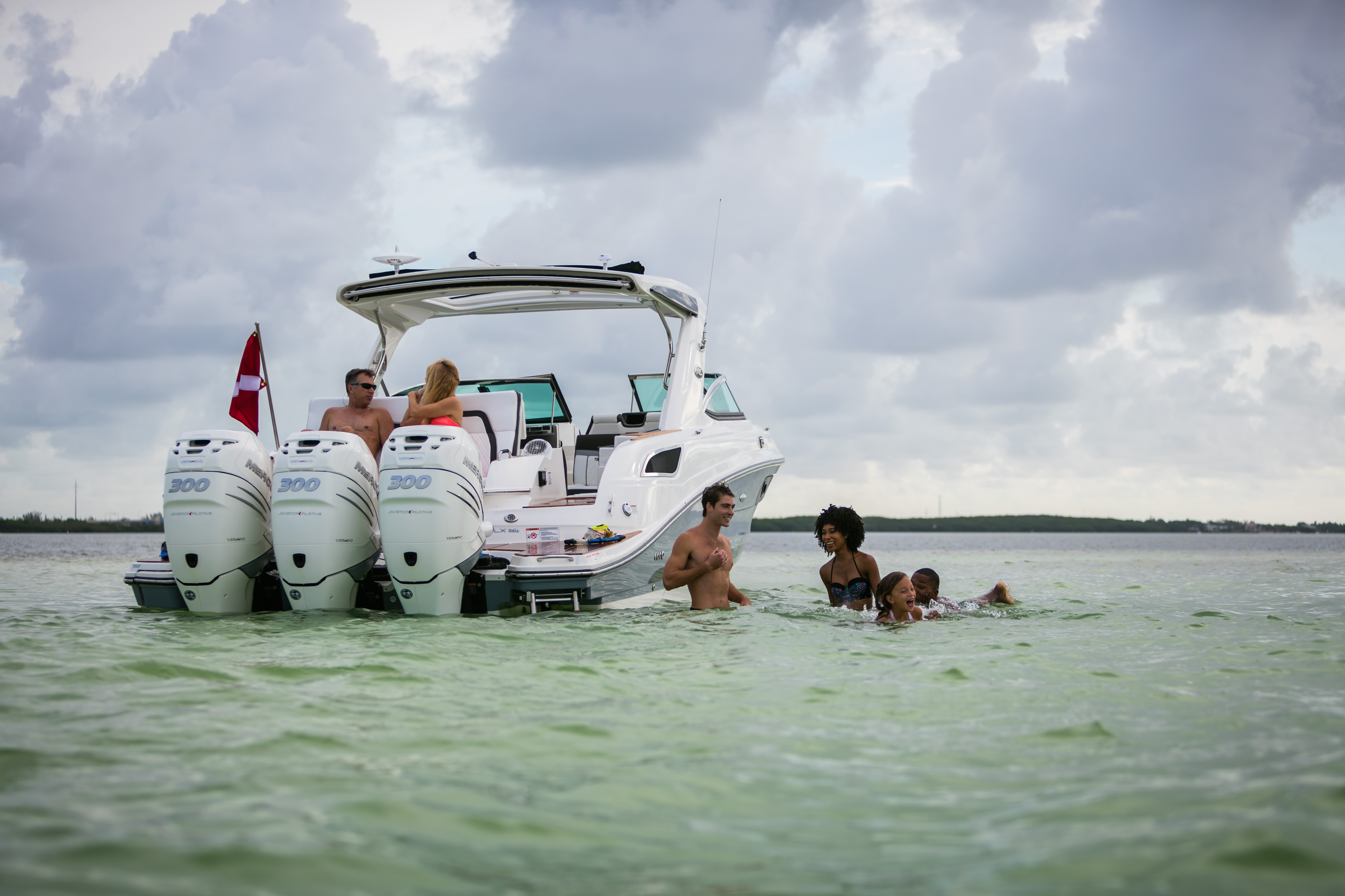 family and friends enjoying swimming off a cabin cruiser in shallow water