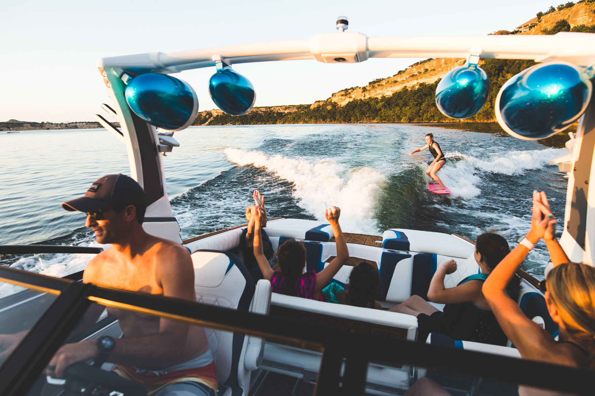 Ski boat with a group of friends towing a wake boarder
