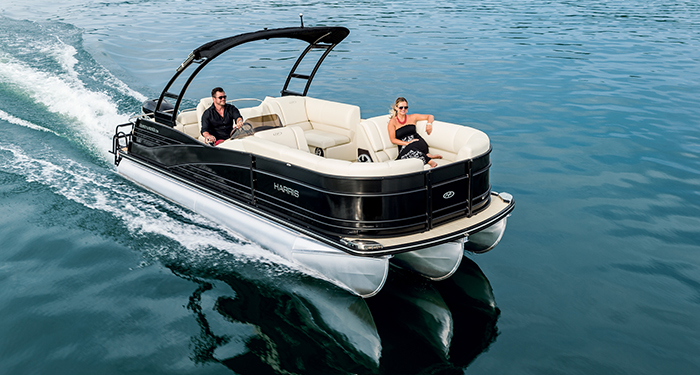 A couple cruising on clear water on a tritoon boat