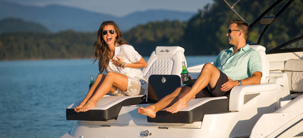 couple lounging on yacht laughing and enjoying drinks
