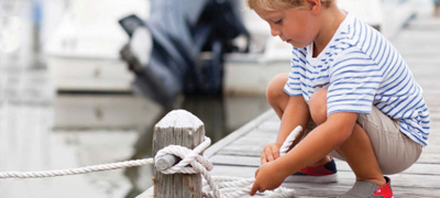 Kid tying the boat to the dock