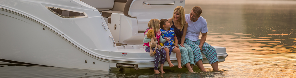 family sitting on rear deck of boat dip their feet in warm afternoon waters