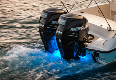 two mercury outboard engines illuminate rear of boat