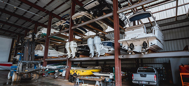 A storage rack holding several boats in three rows, with a pickup truck on the ground in front