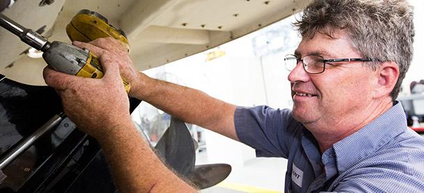 man in uniform servicing boat