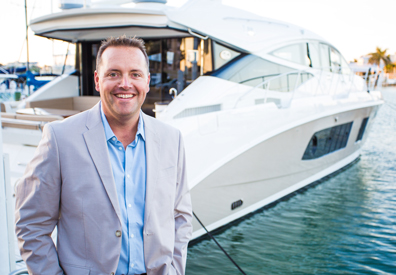 businessman standing in front of charter yacht