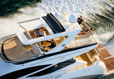 group of people relaxing on second floor of large yacht speeding across the ocean