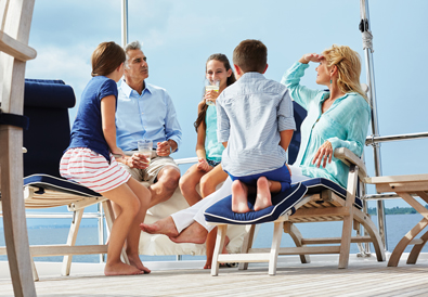 family seated on deck lounge chairs enjoying refreshing drinks