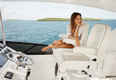 woman seated on luxurious leather chair in yacht anchored outside of nearby island