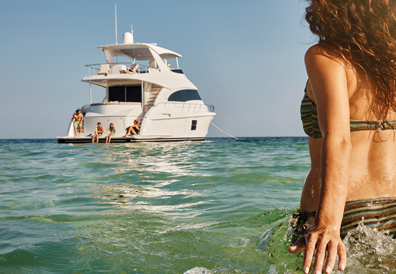Woman watching yacht with friends onboard