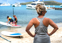 woman standing on beach watching as group in distance prepares for standup paddleboarding