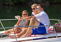 a couple with a young daughter taking a selfie while sitting on the daybed of a boat