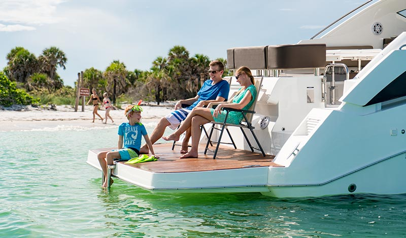 family sitting on swim platform on the aft of an anchored boat