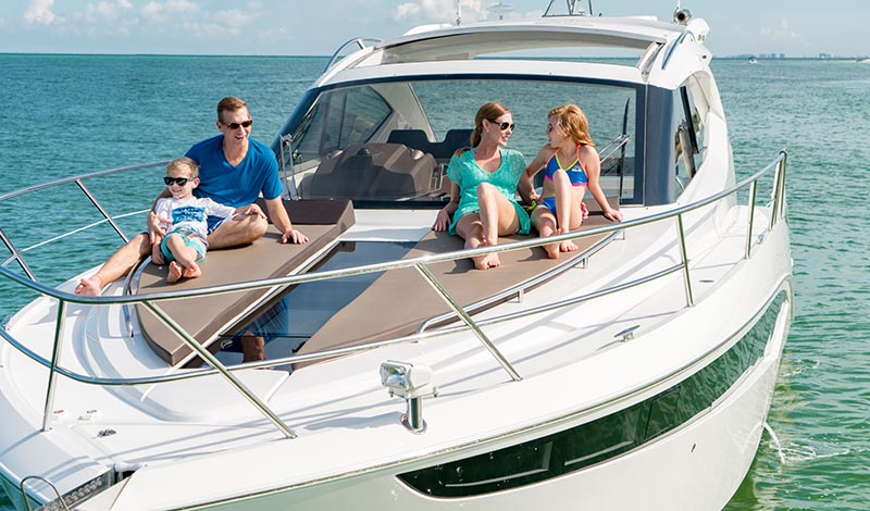 family laying on a sunpad on the bow of a boat