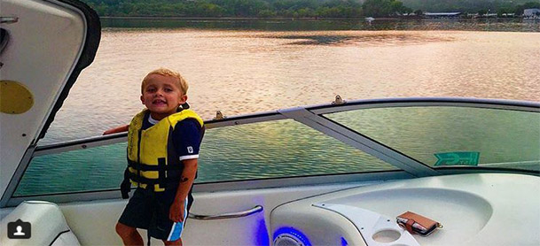 A boy in a yellow life jacket stands on a boat with water behind him