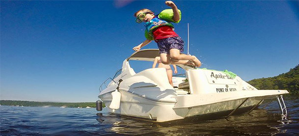 A boy jumps off the stern of a boat into the water