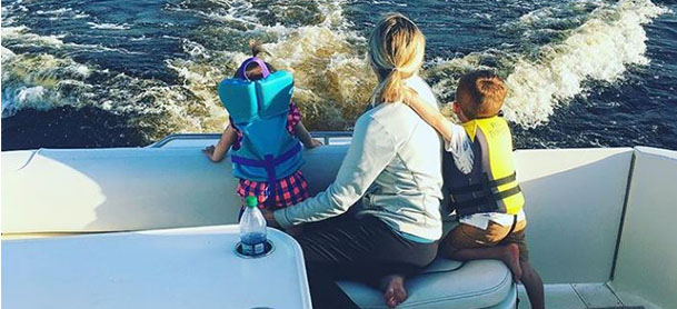 A woman and her two young children look off of a boat as it moves through the water