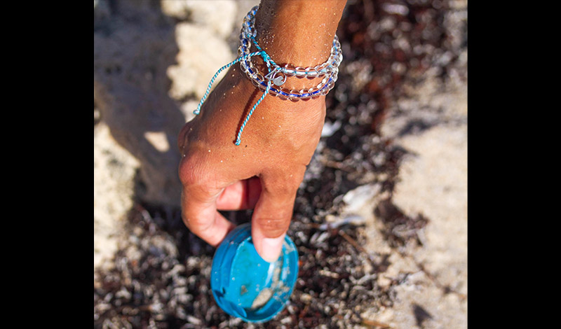 a hand picking up a bottle cap off of the beach while wearing a colorful 4ocean bracelet