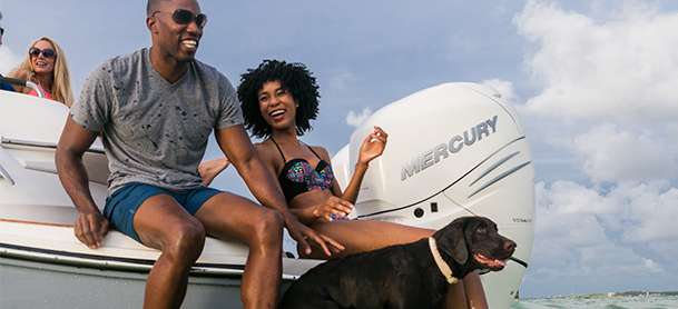Couple and dog on back of boat laughing