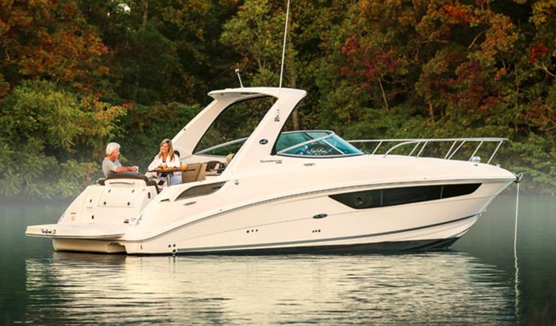 Sea Ray Sundancer anchored with fall foliage behind it.