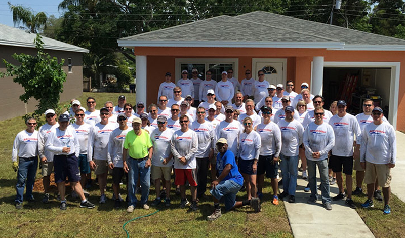 Group of MarineMax employees in front of Habitat For Humanity House