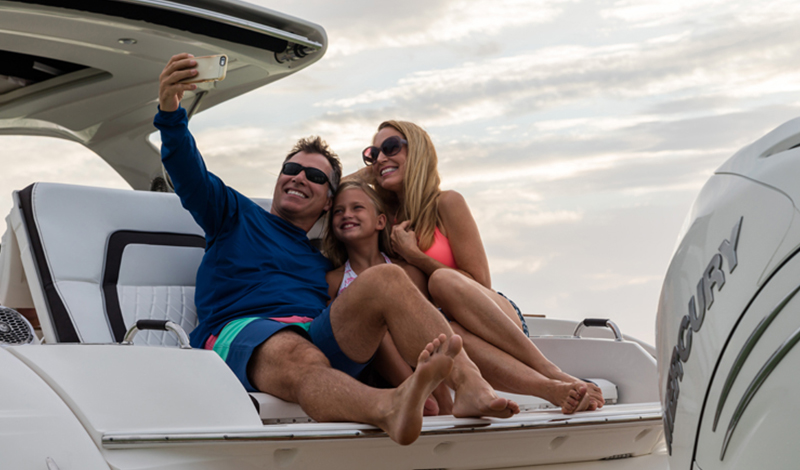 family setting on back of a boat taking a selfie