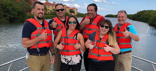 group of people wearing life jackets standing on boat