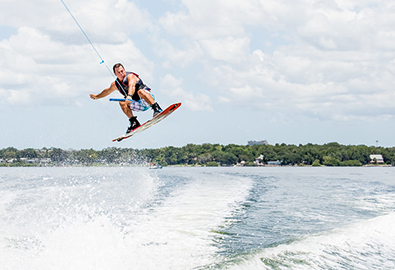 Wakeboarder in air behind boat